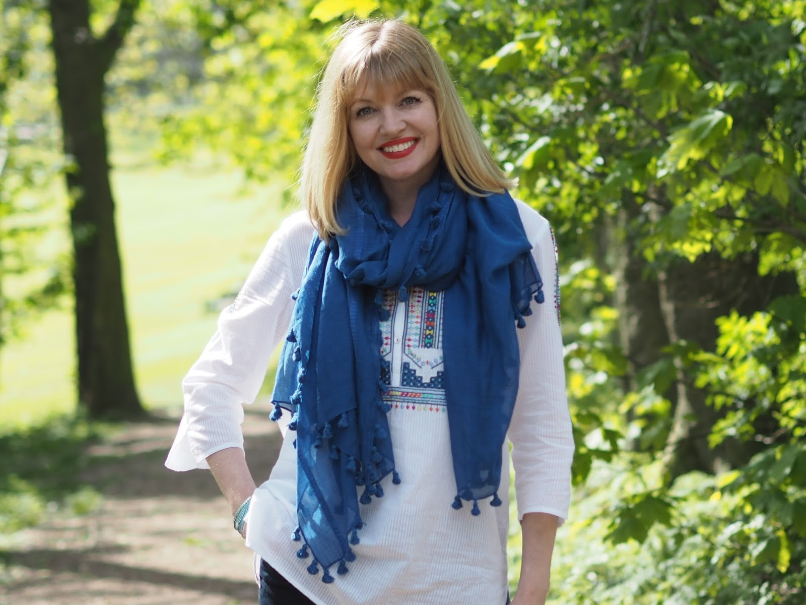 Embroidered white top with skinny jeans, a  marine blue pompom scarf and espadrilles