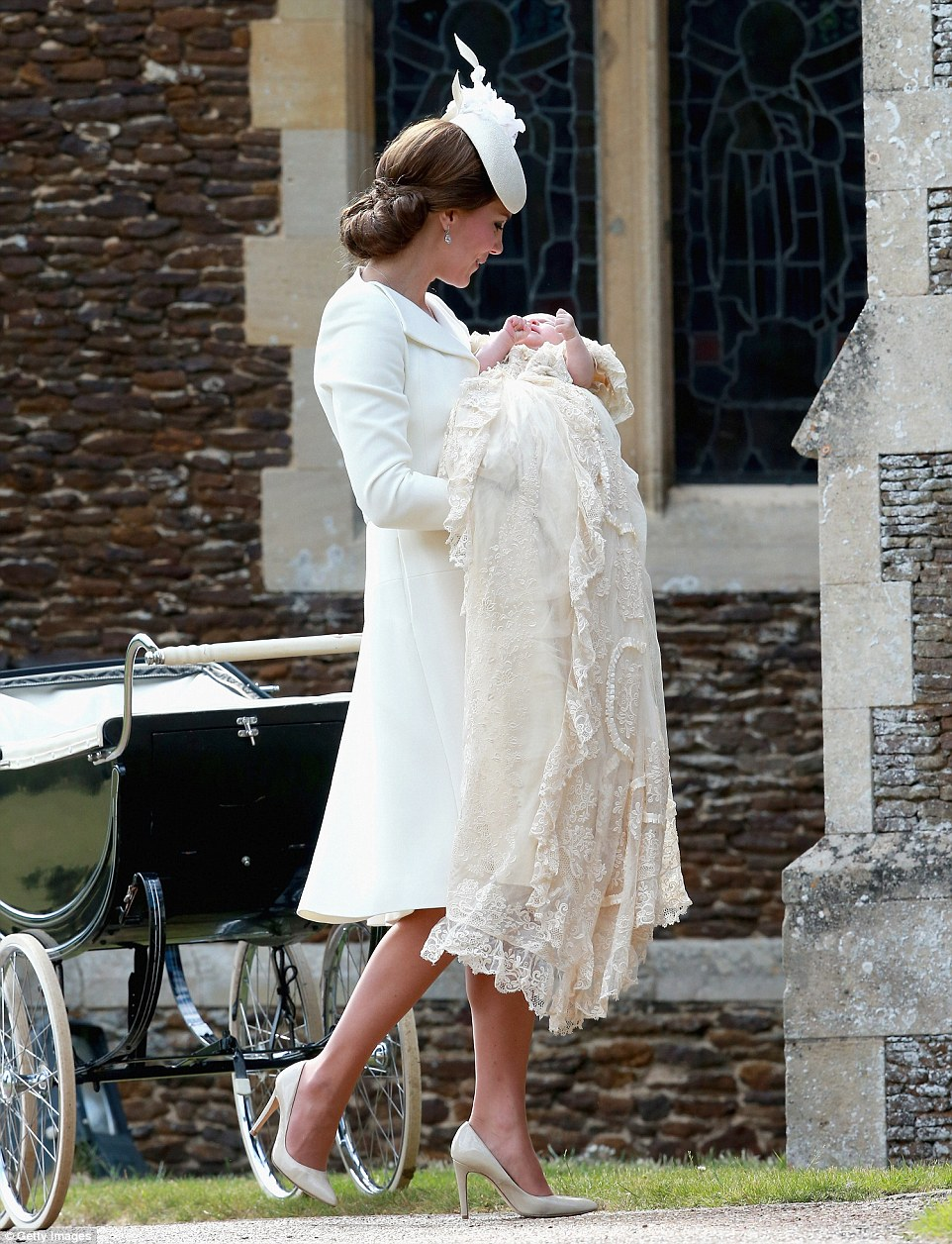 Kate holds Princess Charlotte in her arms as she takes the little girl, dressed in the traditional royal christening gown, into church