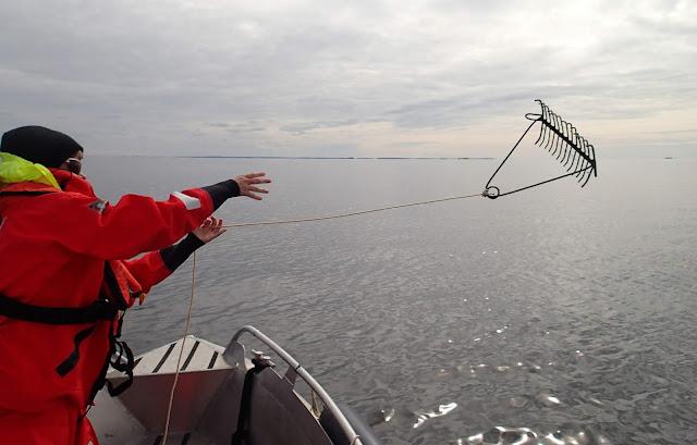 Pelastuspukuun pukeutunut henkilö heittää haraa veneestä.