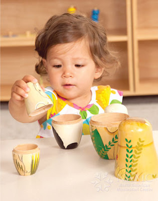 namc montessori developing independence in toddlers girl working with nesting dolls limited choice