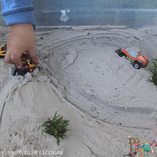 A child driving toy cars in the sand dune small world play