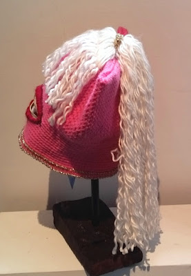 a side view of the Millania Trump Pussyhat. It is bright pink with white wavy woollen locks. The mouth is made of a zipper with crocheted red lips around it. The bottom hem is embellished with gold glitter yarn.