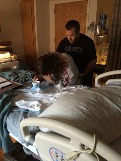 A husband stands behind his wife, who is leaning over a hospital bed in obvious labor, and is applying counter-pressure to her hips during a contraction.