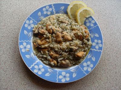 εν πιάτο με λαχαταριστό ρύζι και μύδια γαρνιρισμένο με δύο φέτες λεμόνι
