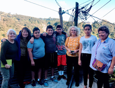Youth and social worker from the local clinic participating in the program on the margin of an urban area. All standing in front of trees and a power line.