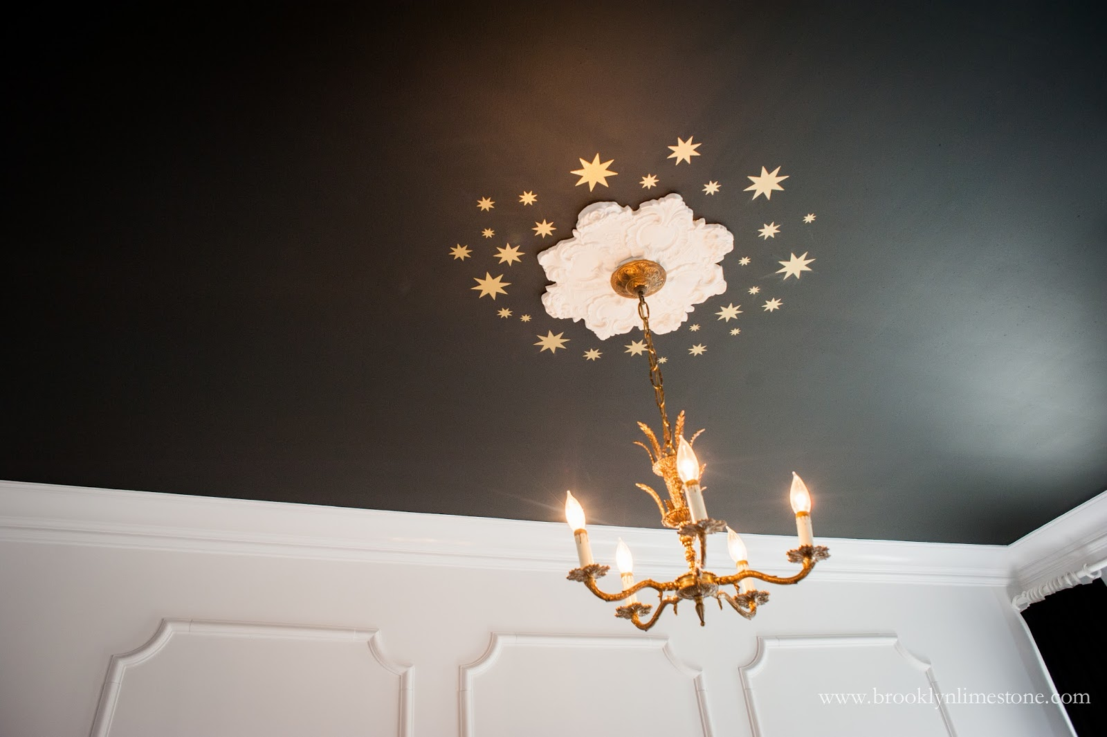 Black ceiling with gold stars and white medallion in girl's bedroom