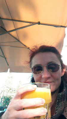 Vrouw met zonnebril drinkt beker verse jus d'orange op een terrasje