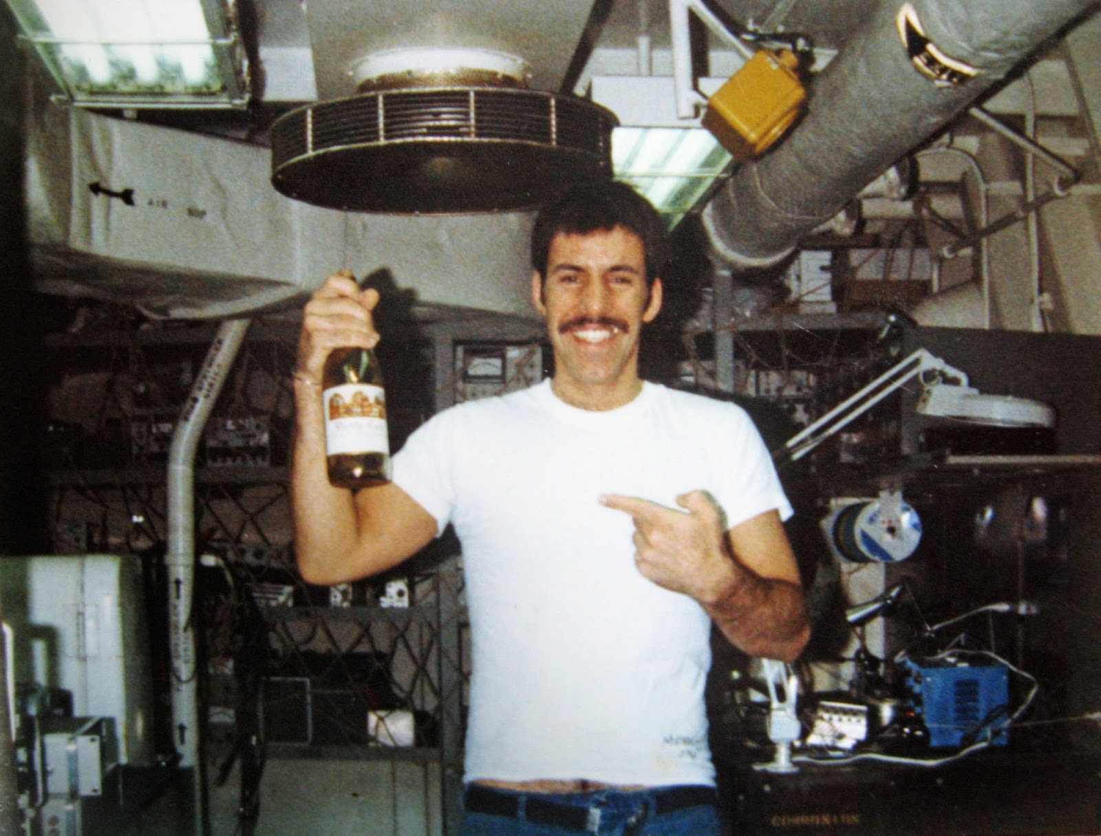 Tommy Mondello aboard Nimitz in shop 670 cal lab with wine bottle & dirt from Jim Morrison'd grave 1983