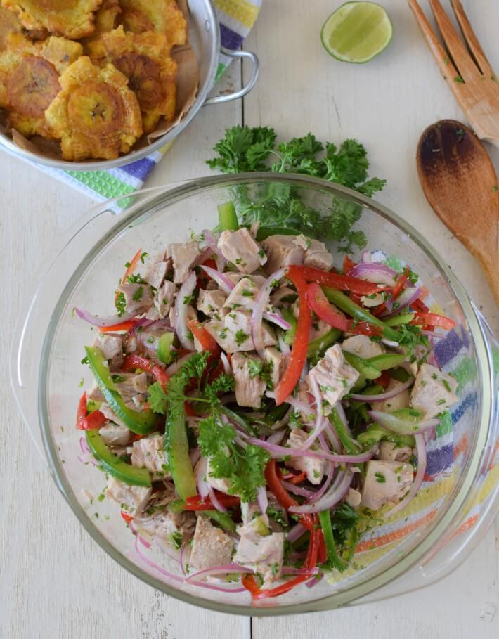 Atún cocido preparado en escabeche con cebolla morada, pimentones y perejil