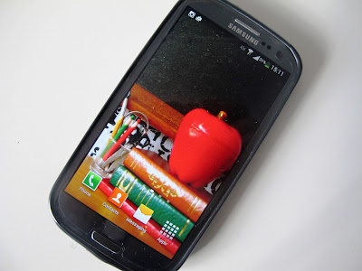 Mobile phone withg wallpaper depicting a modern dolls' house scene of a pile of books with a large apple on top, and a jar of pens and pencils next to it.
