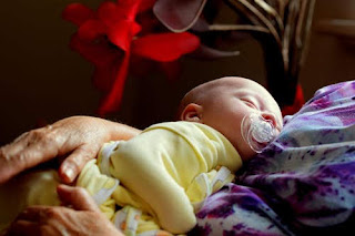 رضيع نائم في حضن أمه