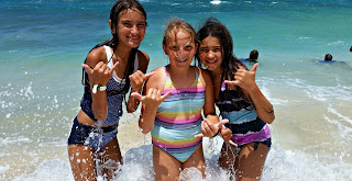 "Three girls at Aloha Beach Camp's Hawaii summer camp standing together on the beach giving the ""Hang Loose"" sign with the ocean in the background."