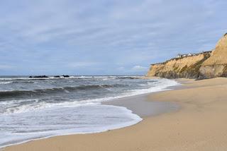 Breaking waves at the foot of golden cliffs, Half Moon Bay, California
