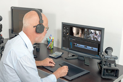 Pic of man sitting in front of video editing programme on screen and handheld camera on desk