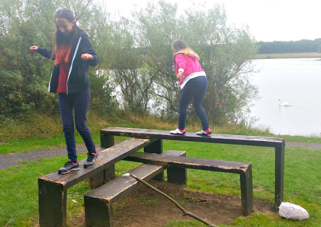 My two girls climbing and balancing on planks of wood next to a lake