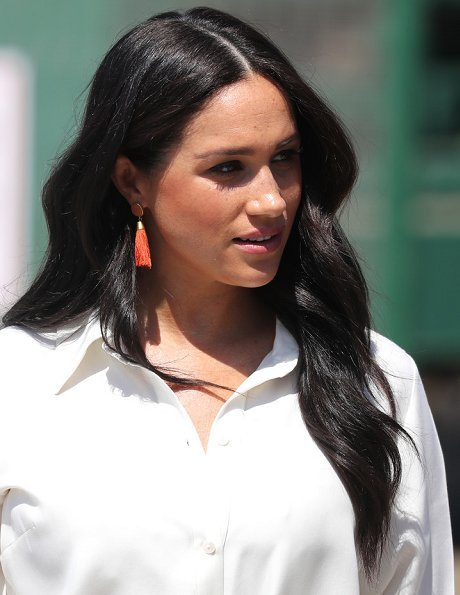 Meghan Markle wore a white belted shirt dress, and Madewell stone and tassel earrings, Stuart Weitzman suede pumps