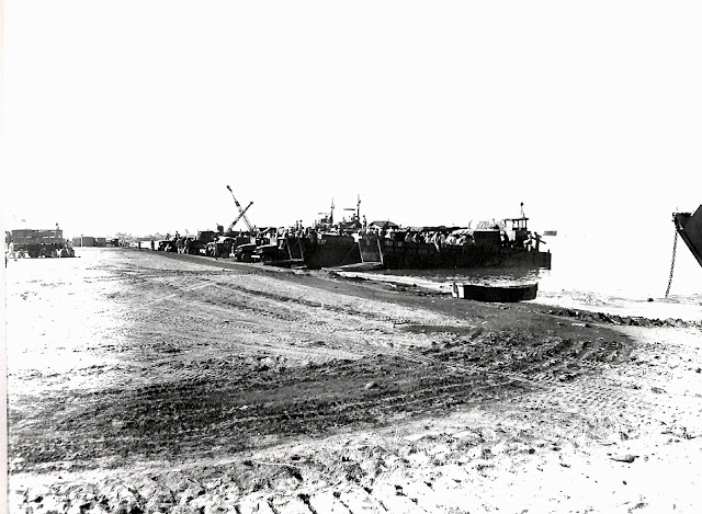The LCM's (Landing Craft Mechanized) with (unreadable) on the landing beach at Batangas Bay, Base R,  Batangas, Luzon, P.I. Port (unreadable). Taken 29 June 1945.