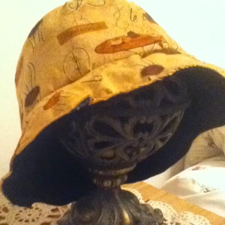 Brimmed hat out of brown tea-table patterned fabric. The hat's lining is black.
