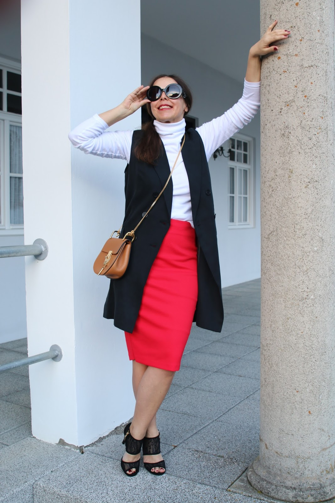 Outfit white turtleneck, black Prada glasses, black long vest, red midi skirt, black lace heels