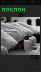 несколько мужчин в белых одеждах совершают поклон во время моления