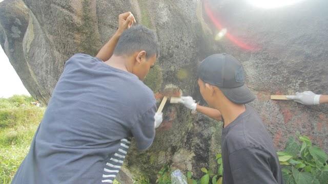 Menginspirasi, Pemuda  Membersihkan Coretan di Batu Bukit Jamur Bengkayang
