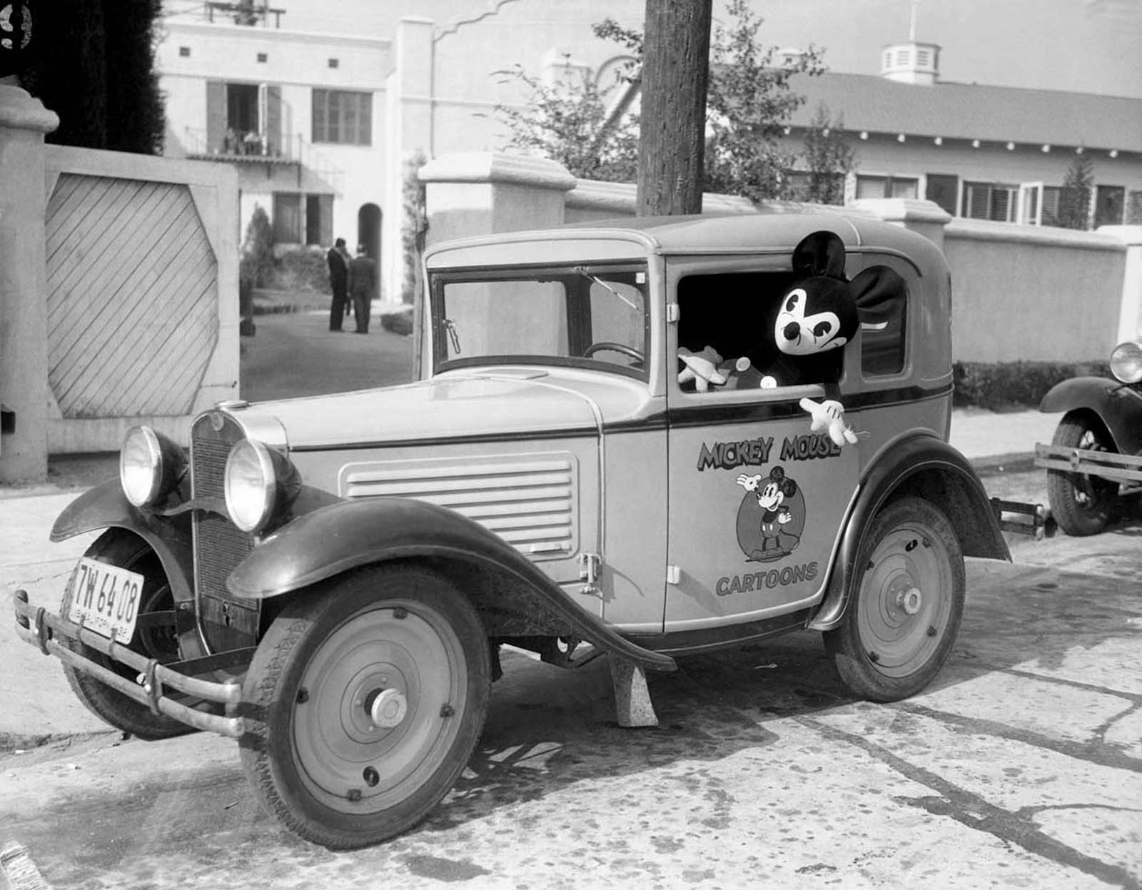 Mickey at the wheel of his own car, bearing his personal coat of arms, at the studio. 1933.