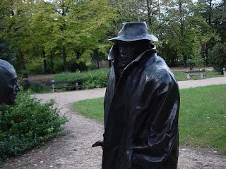 estatua de homem de sobretudo e chapeu