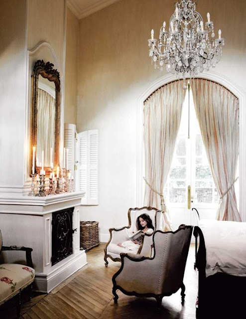 Travel Themed Decor Bedroom with Armchairs Crystal Chandelier Fireplace Candle Large Wall Mirror Bay Windows Hardwood Floors
