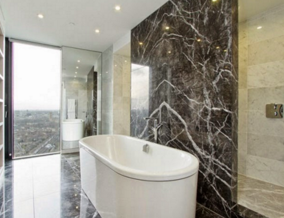 Marble bathroom with panoramic views of the outdoor landscape.