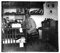 man seated at a desk in a room with bookshelves on the wall