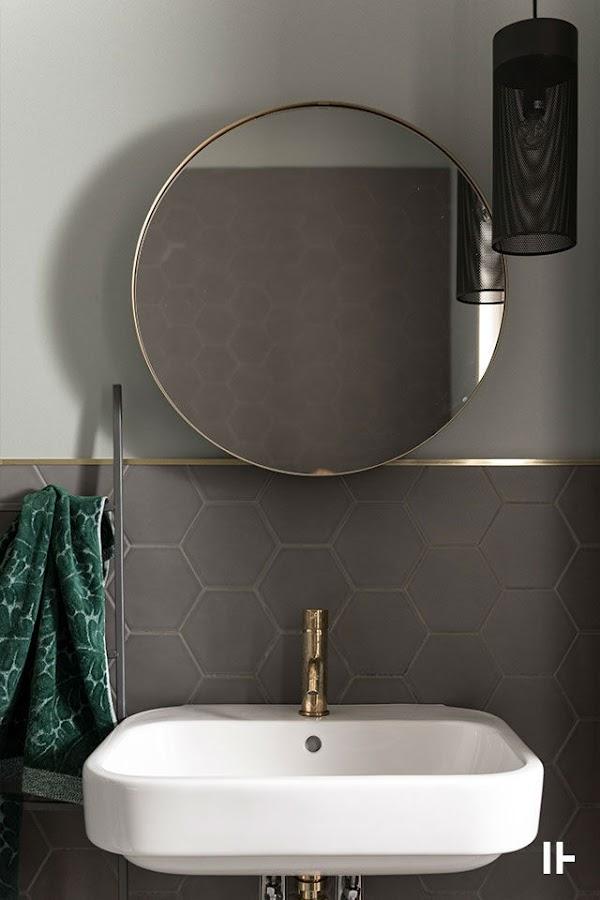 baño con espejo circular y grifería en dorado