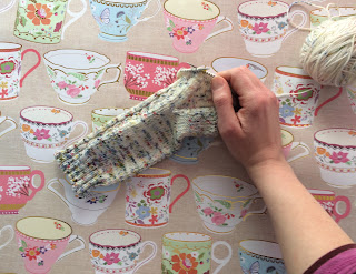 Knitting a pair of socks against a backdrop of teacups
