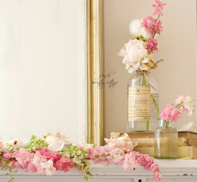 Cottage garden larkspur flowers in glass soap bottles on mantel