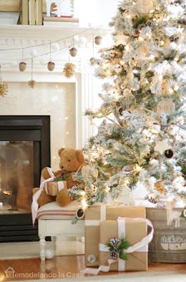 Christmas tree with teddy bear by its side, close to mantel