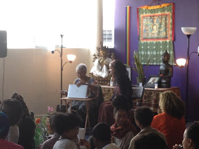 Black women on meditation mats look on as Alice Walker and Spring Washam speaks