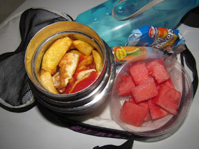 Nigerian school lunchbox meal of FRIES WITH KETCHUP AND EGGS SERVED WITH WATERMELON SLICES