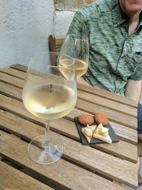 Glass of white wine and snacks on Piazza del Barbacan in Trieste