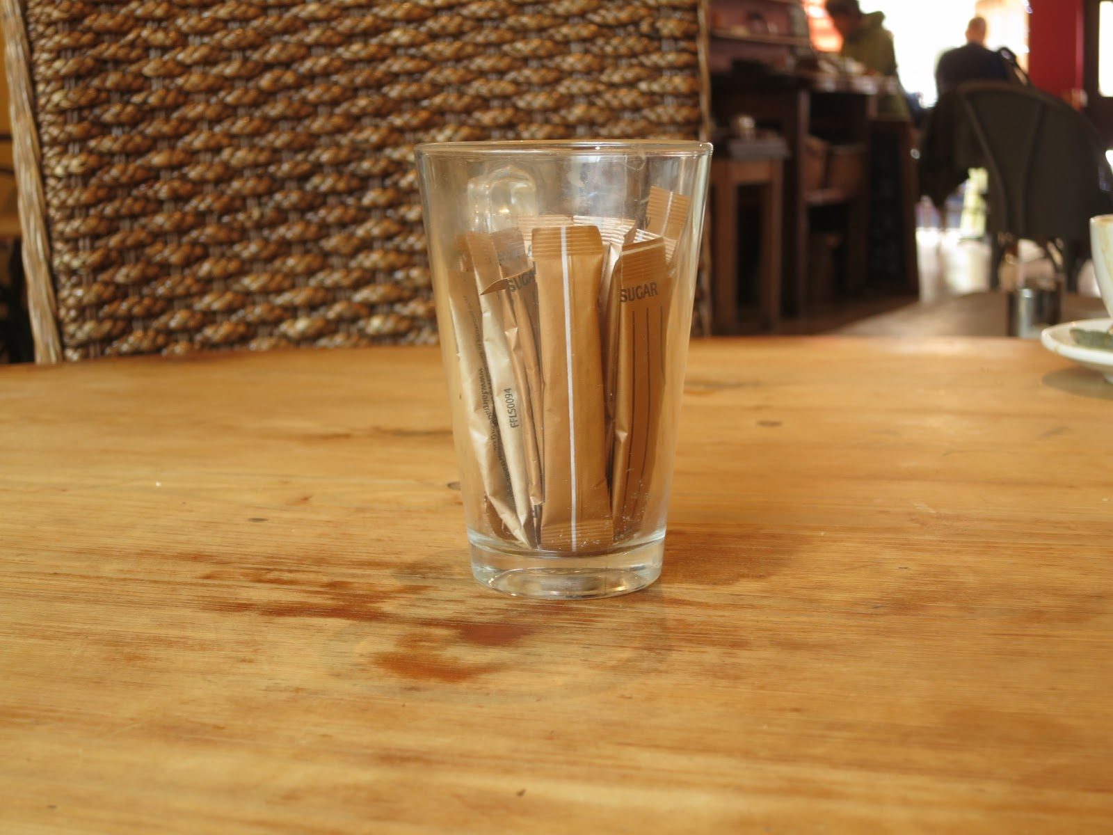Water glass containing thin packets of sugar on a wooden table beside a wicker backed chair in cafe.