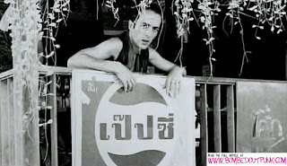 Joe Strummer above a Thai Pepsi sign in Bangkok in 1982   Pennie Smith
