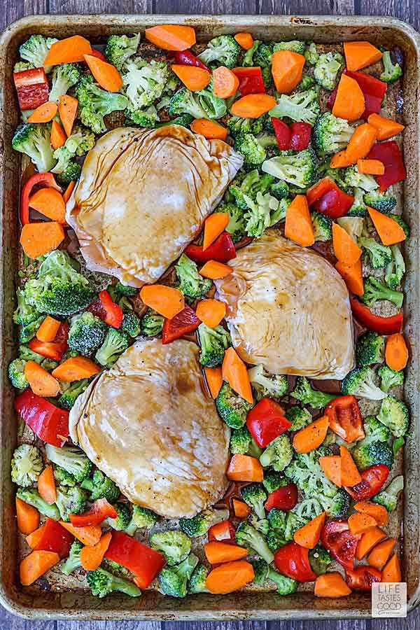 Chicken thighs and vegetables on sheet pan ready to bake for Baked Teriyaki Chicken Thighs