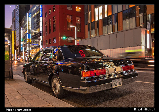 Dark blue Toyota Century parked on Kerb, Ginza, Japan, under neon light.
