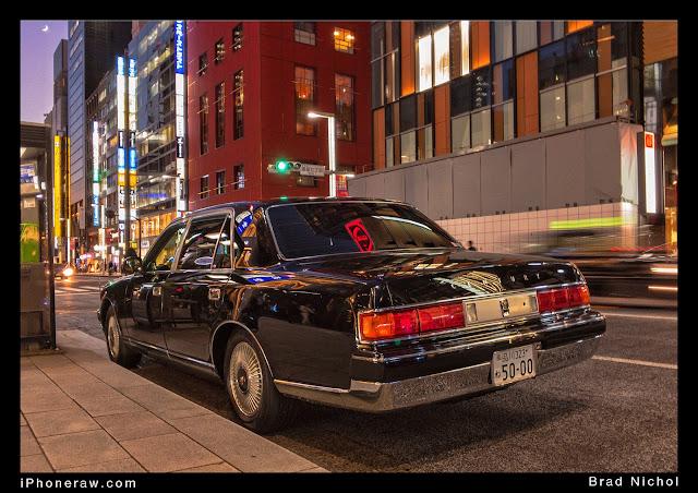 Dark blue Toyota Century parked on Kerb, Ginza, Japan, under neon light.