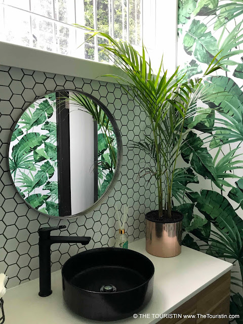 Lavishly decorated bathroom with black sink and plant wallpaper