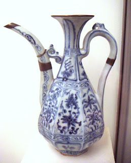 A tall, slender teapot or pitcher with an intricate floral design and some gold or copper around the edges.
