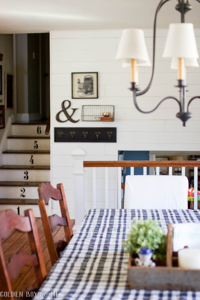 farmhouse style dining room with planked walls and numbered stairs