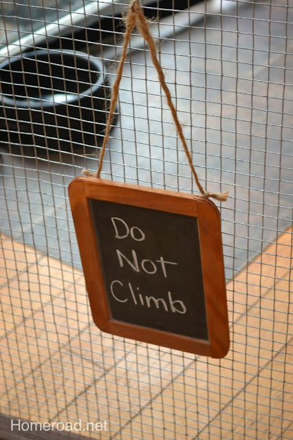 Chalkboard hanging on fence says Do not climb
