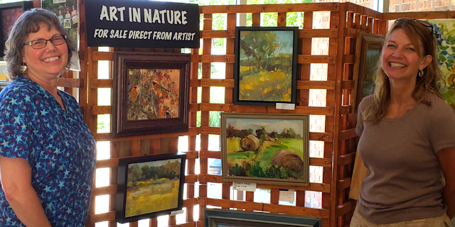 Artists Carol Foster and Lisa Riedl at Crabtree Nature Center's art display.