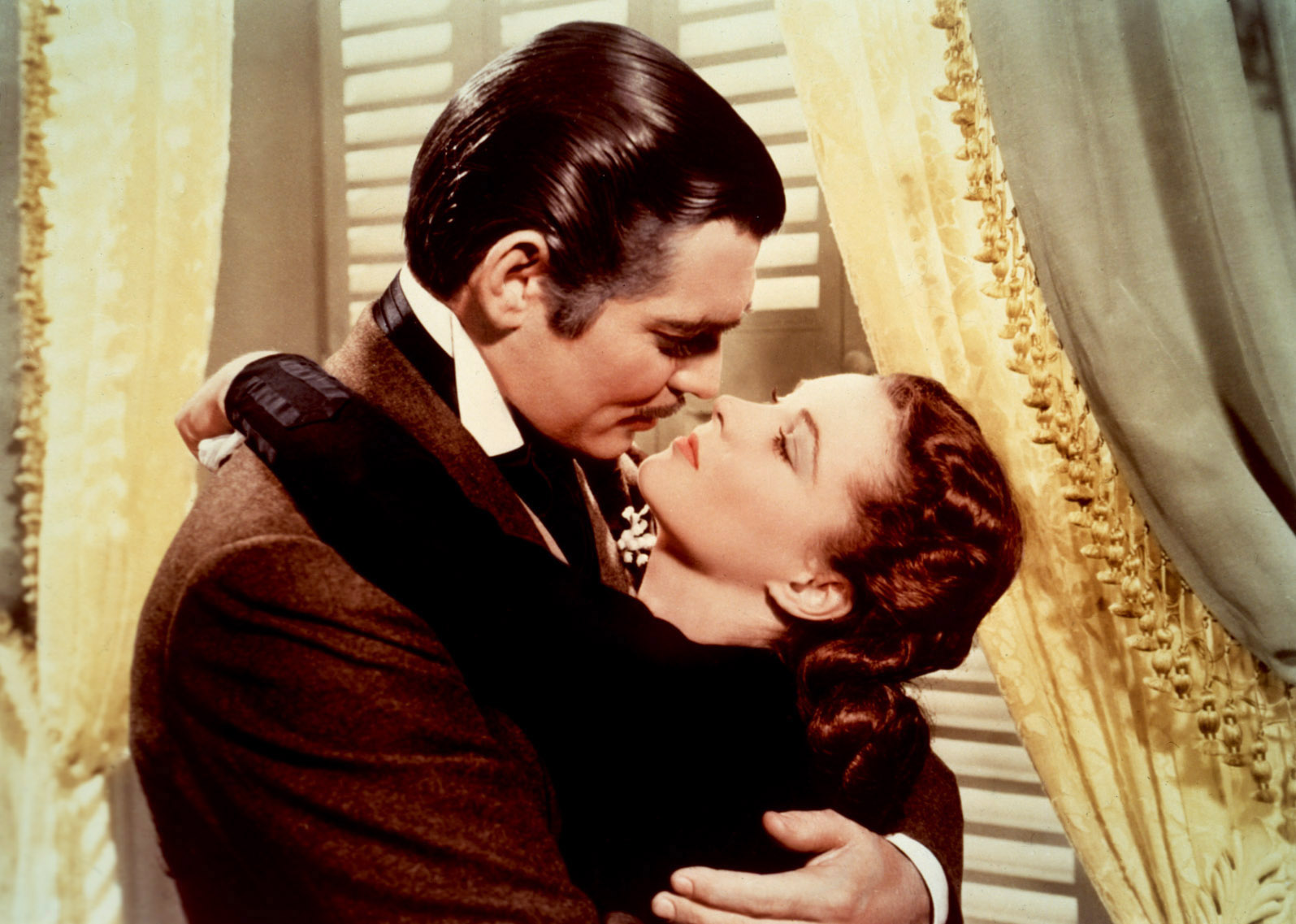 Clark Gable as Rhett Butler embracing Vivien Leigh as Scarlet O'Hara in Gone with the Wind movieloversreviews.filminspector.com