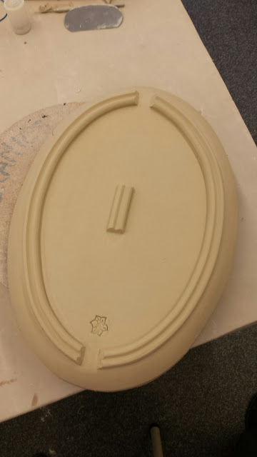 Bottom of oval serving platter in clay / pottery.