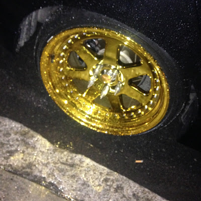 Fancy gold plated car rims as seen near Forest Hills